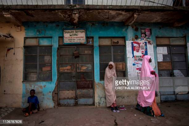 TOPSHOT First voters wait on the streets of Kaduna on February 23 ahead of the opening of polling stations as Nigeria votes to elect its new...