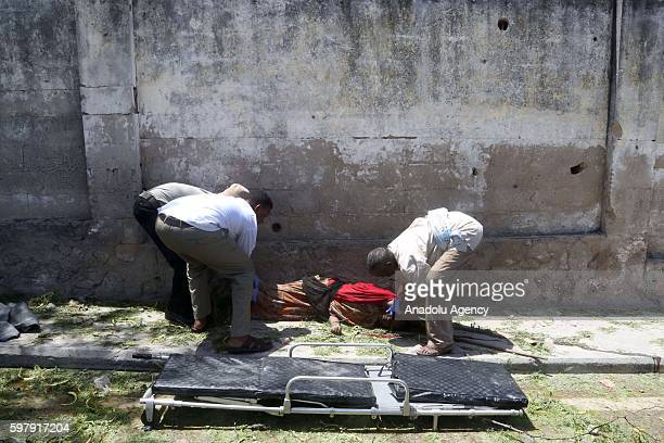 Firstaid members carry a bomb attack victim at the site of a car bomb attack near a Presidental Palace at SYL Hotel in Somalia's capital Mogadishu on...