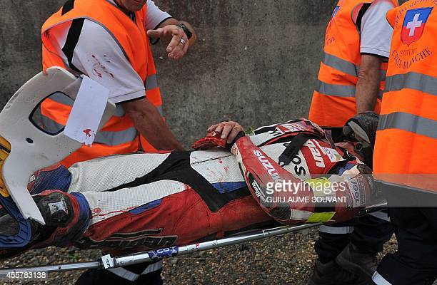 Firstaid workers carry France's David Dumain rider of the Suzuki GSXR N°63 on a stretcher after he crashed during the 37th Le Mans 24 hours endurance...