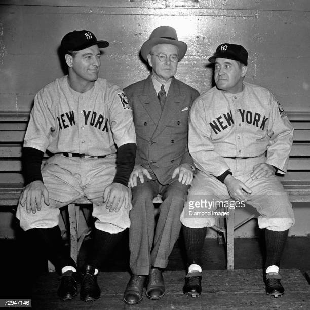 Firstbaseman Lou Gehrig of the New York Yankees John Hillerich of Hillerich and Bradsby and Yankees' manager Joe McCarthy pose on the bench prior to...