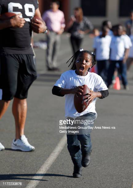 Firstgrader Kiara McCoy runs with the ball during the Oakland Raiders 16th annual NFL/United Way Hometown Huddle at Parker Elementary School in East...