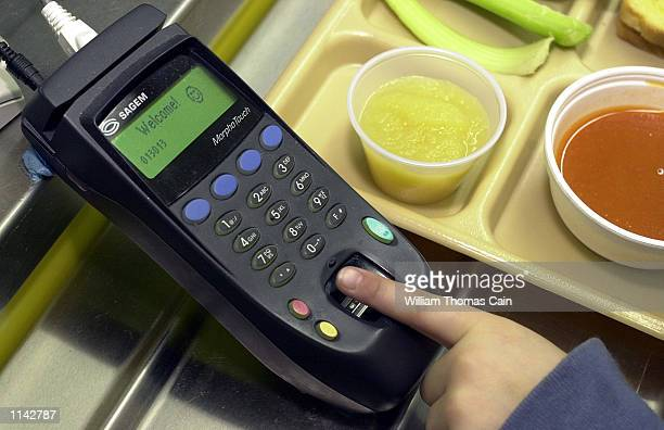 A firstgrader places a finger on the fingerprint scanner to pay for lunch at Penn Cambria PrePrimary School March 1 2002 in Cresson Pa Penn Cambria...