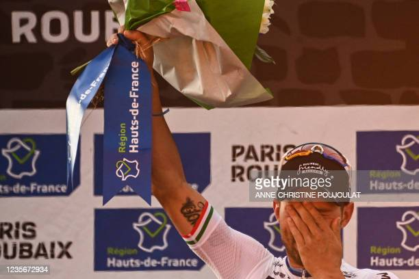 First-placed Bahrain Victorious Sonny Colbrelli from Italy celebrates on the podium after competing in the 118th edition of the Paris-Roubaix one-day...