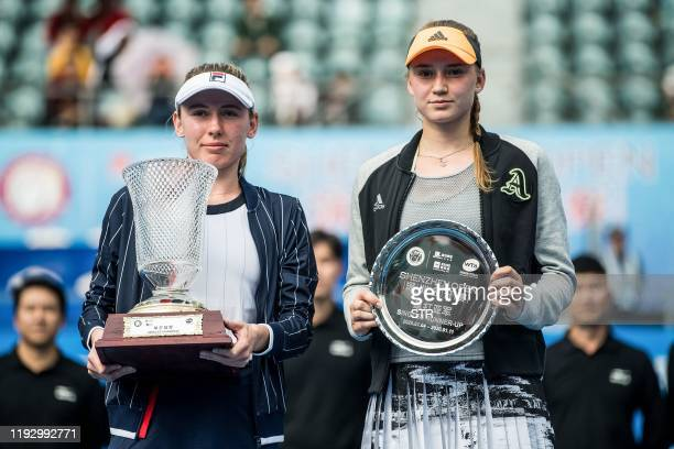 Firstplaced Ekaterina Alexandrova of Russia poses for photos with secondplaced Elena Rybakina of Kazakhstan after their women's singles final match...