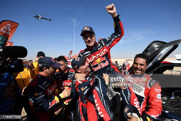 TOPSHOT Firstplaced for the auto category JCW XRAID Mini Team Spain's driver Carlos Sainz celebrates as he is congratulated by secondplaced Toyota's...