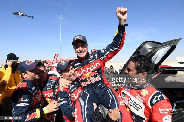 Firstplaced for the auto category JCW XRAID Mini Team Spain's driver Carlos Sainz celebrates as he is congratulated by secondplaced Toyota's team...