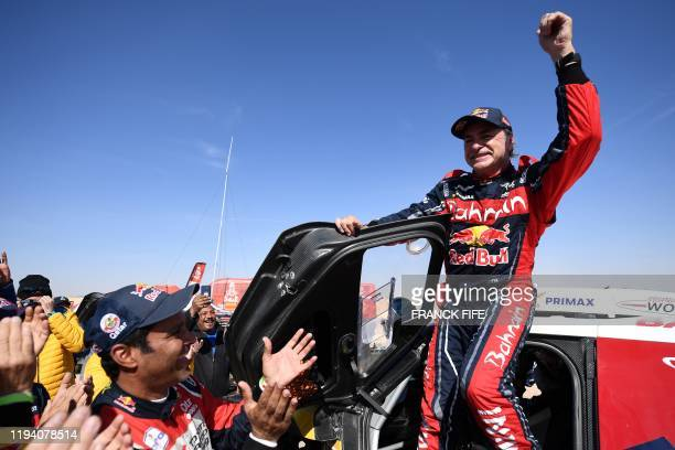Firstplaced for the auto category Mini JCW XRAID Team Spain's driver Carlos Sainz celebrates as he gets out of his car while secondplaced Toyota's...