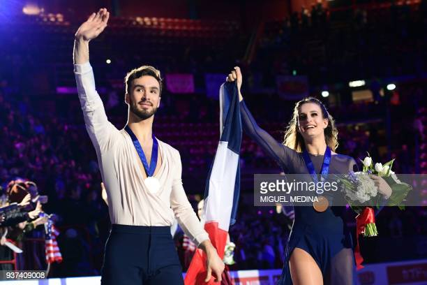 Firstplaced France gold medallists Gabriella Papadakis and Guillaume Cizeron celebrate and wave at the audience during the podium ceremony after...