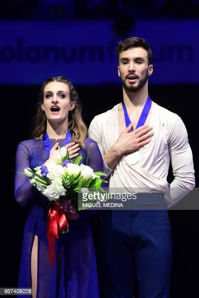 Firstplaced France gold medallists Gabriella Papadakis and Guillaume Cizeron sing the national anthem on the podium during the price ceremony after...
