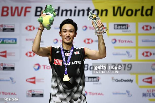 Firstplaced Japan's Kento Momota poses with his gold medal during the podium cermony after his victory over Denmark's Anders Antonsen during the...