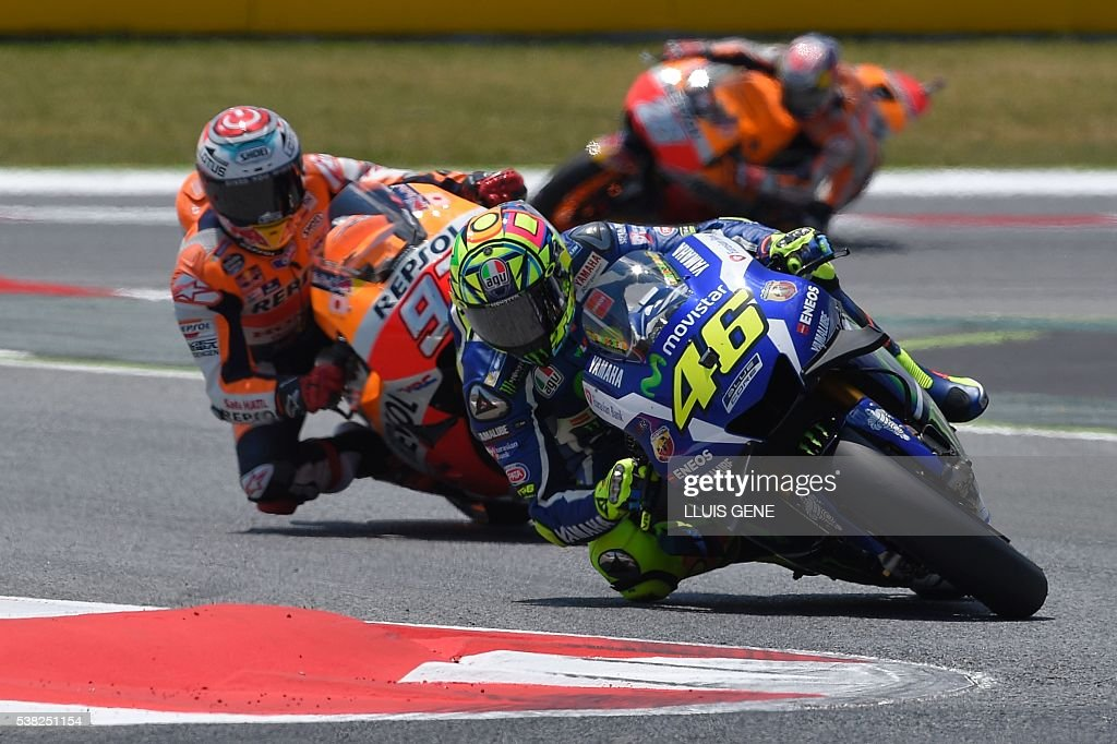 First-placed Movistar Yamaha MotoGP's Italian rider Valentino Rossi (R) followed by second-placed Repsol Honda Team's Spanish rider Marc Marquez (L) and third-placed Repsol Honda Team's Spanish rider Daniel Pedrosa rides during the MotoGP race of the Catalunya Grand Prix at the Montmelo racetrack near Barcelona on June 5, 2016. / AFP / LLUIS