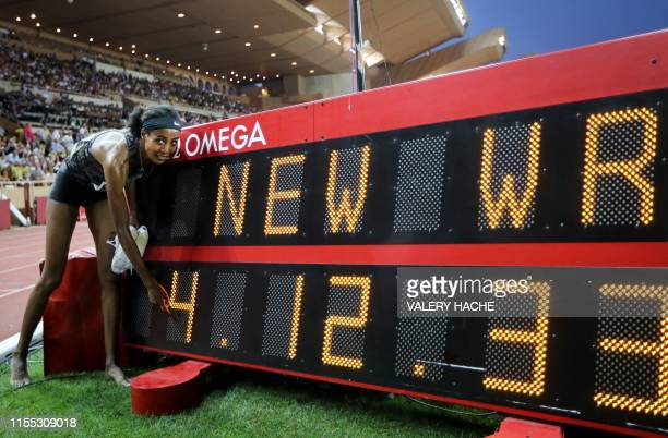 First-placed Netherland's Sifan Hassan poses in front of a screen reading her new world record in the Women's 1 mile during the IAAF Diamond League...