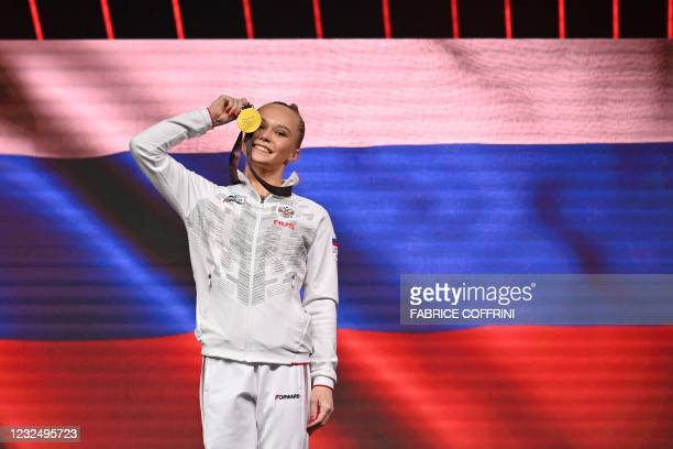 First-placed Russia's Angelina Melnikova celebrates on the podium during the award ceremony after competing in the Women's uneven bars apparatus...