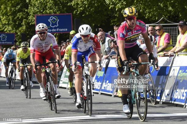 Firstplaced team JumboVisma Dutch cyclist Dylan Groenewegen crosses the finish line during the third stage between SaintQuentin to Compiegne of the...