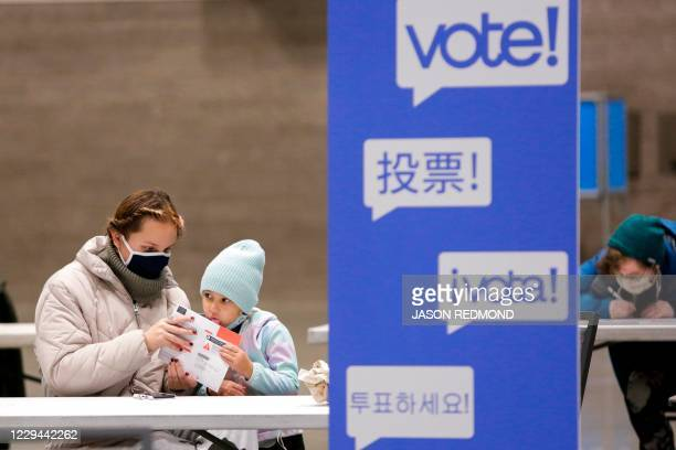 First-time voter Alexis Castaneto gets help from her daughter Luna sealing her envelop at a temporary voting center at the CenturyLink Field Event...
