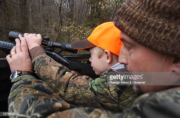 Fischer Pearson peers through the scope of his rifle while hunting with his father Brad Pearson December 21 2010