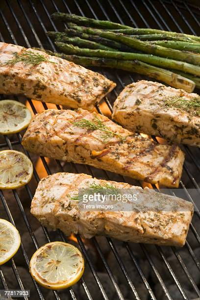 Fish and asparagus cooking on grill