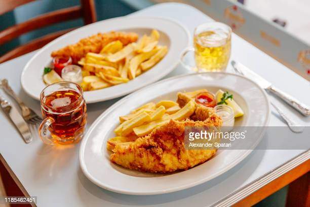 fish and chips on plate and beer served on the table - alcohol stock pictures, royalty-free photos & images