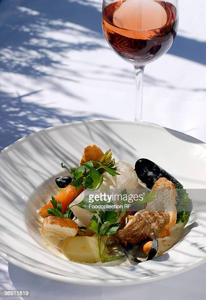 Fish and shellfish with vegetables in plate with glass of rose wine, close-up