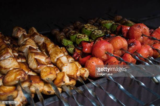 Fish and vegetable skewers are grilled at shashlik barbecue lunch for passengers of river cruise ship