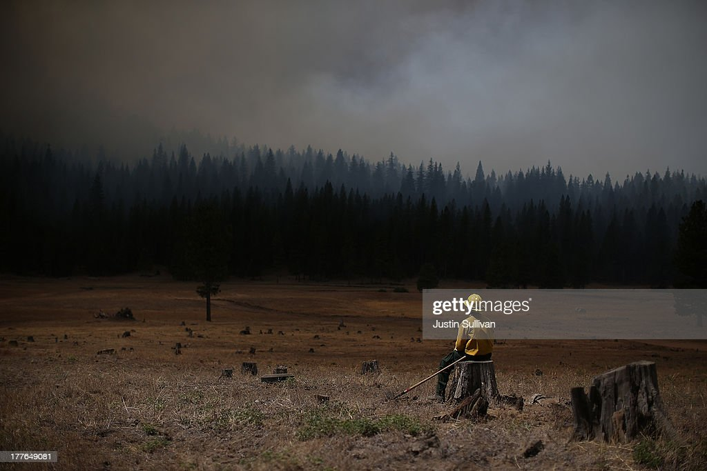 U.S. Fish and Wildlife Service firefighter Corey Adams sits on a tree stump as he monitors the Rim Fire on August 25, 2013 near Groveland, California. The Rim Fire continues to burn out of control and threatens 4,500 homes outside of Yosemite National Park. Over 2,000 firefighters are battling the blaze that has entered a section of Yosemite National Park and is currently 7 percent contained.