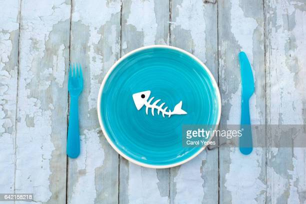 fish bone skeleton in a blue plate on table - animal bones stock photos and pictures