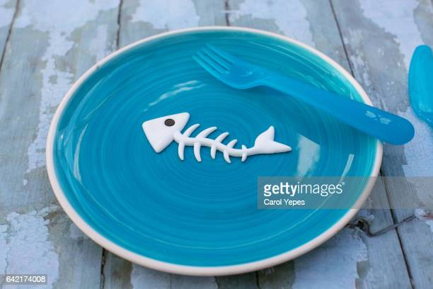 fish bone skeleton in a blue plate on table - fish skeleton stock photos and pictures