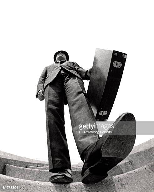 fish eye angle of salesman walking down stairs foot about to step on camera briefcase elongated body distortion tall big. - wide angle stock pictures, royalty-free photos & images