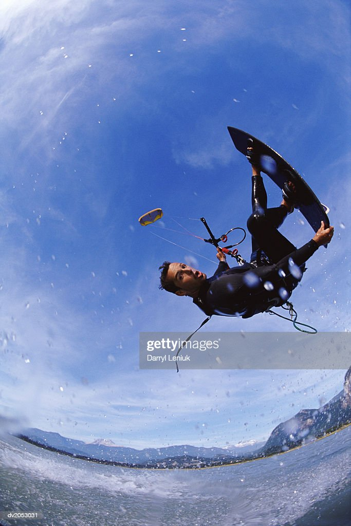 Fish Eye Lens Shot of a Kite Surfer Performing a Stunt in Mid Air : Stock Photo