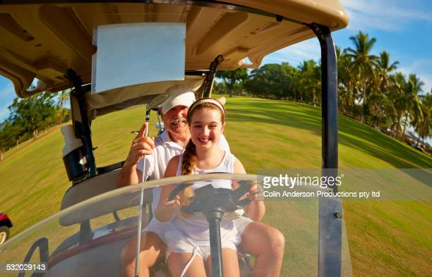 Fish eye view of Caucasian golfer driving golf cart with granddaughter