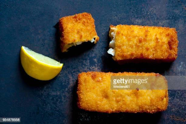 Fish fingers and lemon slice on dark metal