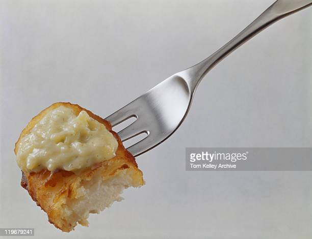 Fish fingers with savoury sauce in fork close-up