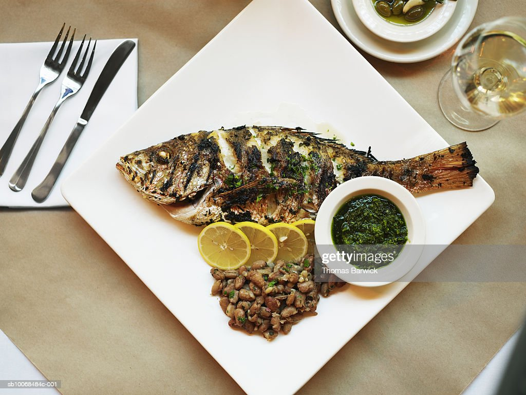 Fish grilled with salsa verde and cranberry beans, close-up : Stock Photo