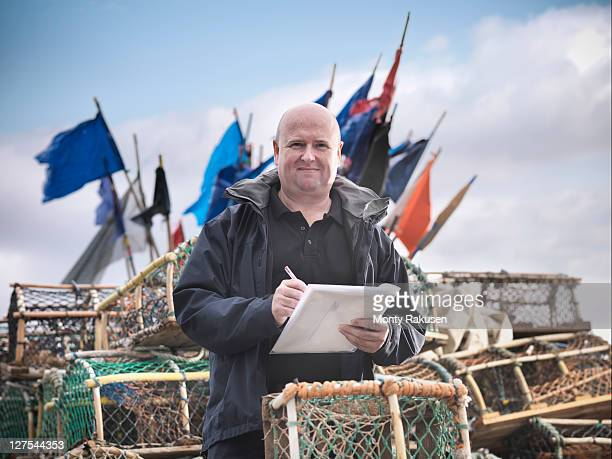 fish inspector with lobster pots - monty rakusen stock pictures, royalty-free photos & images