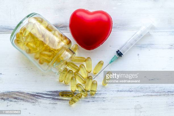 fish oil capsules with omega 3 and vitamin d in a glass bottle on wooden texture, healthy diet concept,close up shot. - omega 3 stock pictures, royalty-free photos & images
