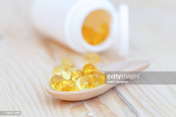fish oil capsules with omega 3 and vitamin d on spoon wood with wooden background, healthy diet concept. - letra d - fotografias e filmes do acervo