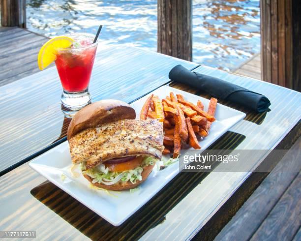 fish sandwich, french fries, red cocktail - uferviertel stock-fotos und bilder