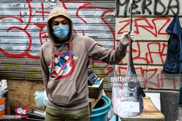A fish seller wears a mask and holds the swordfish head in his hand during the first day of reopening of the historic fish market in Catania called a...