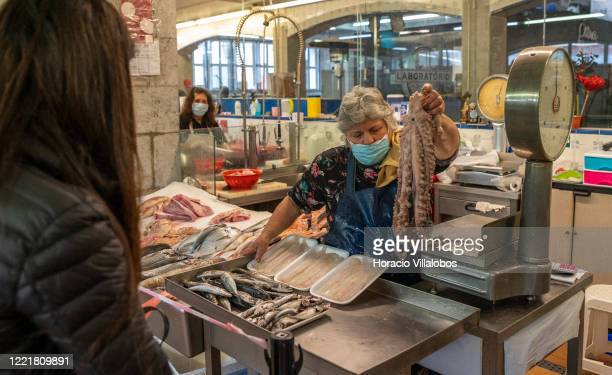 Fish stall vendor wears a protective mask while weighing octopus for a waiting shopper in the Mercado da Vila, the city main municipal market, where...