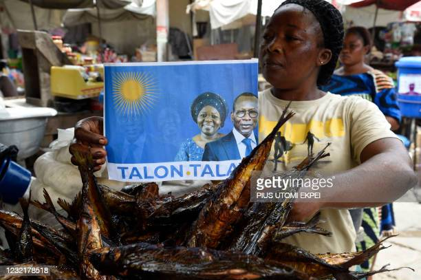 Fish vendor holds a poster with photographs of incumbent Benin President Patrice Talon and running mate Mariam Talata at the market in Cotonou on...