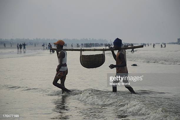 Fish vendors return with fresh fish bought from a trawler Dublar Char Sundarban Khulna Bangladesh 2008