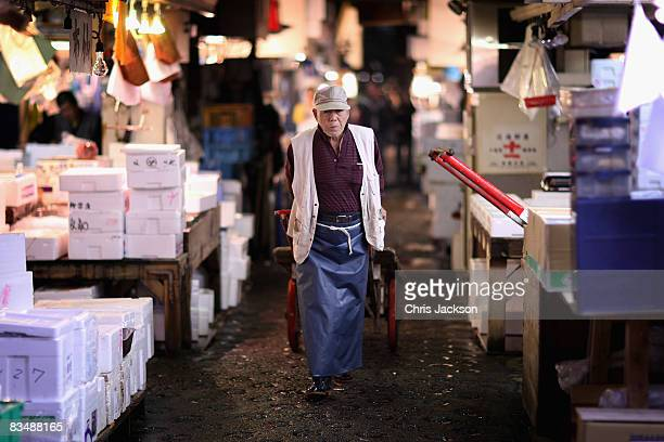 A fish worker pulls his cart through the narrow lanes of Tsukiji Fish Market on October 30 2008 in Tokyo Japan The market handles approx 2888 tons of...
