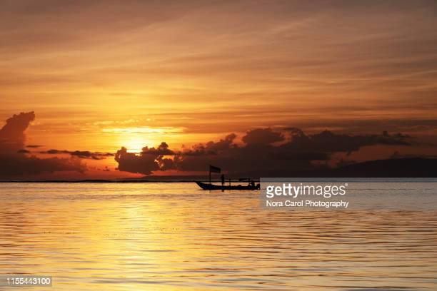 fisheman boat during sunrise in sanur bali - インド洋 ストックフォトと画像