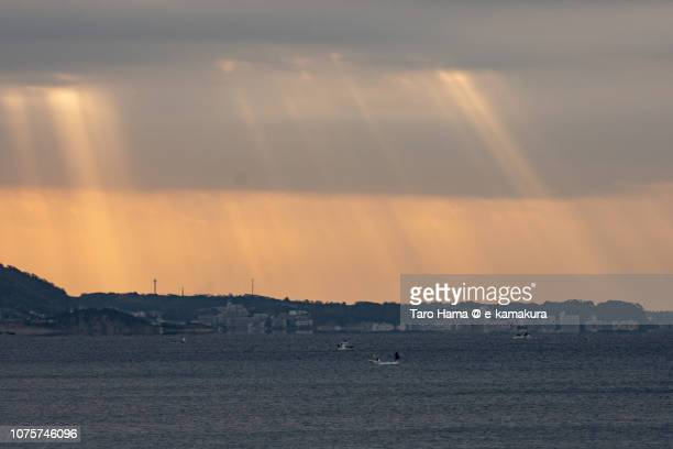 Fisher boat and morning sunbeam on residential buildings in Yokosuka cities and Sagami Bay in Kanagawa prefecture in Japan