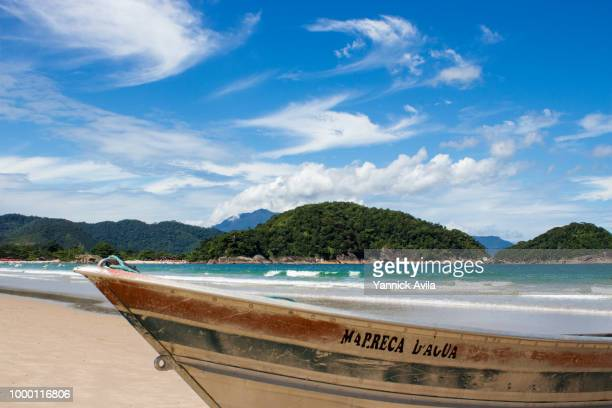 A fisher boat stationed in the sand in a sunny day in Ubatuba, Sao Paulo
