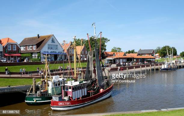 Fisher boats are anchored at the harbour of Greetsiel on August 14 2017 in Bremerhaven nothern Germany / AFP PHOTO / PATRIK STOLLARZ