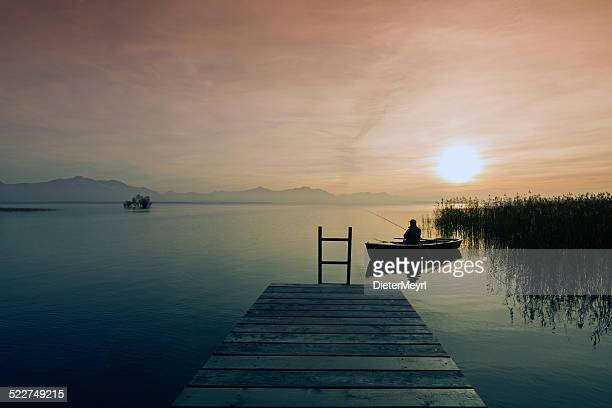 fisher in  boat at dusk - upper bavaria stock photos and pictures
