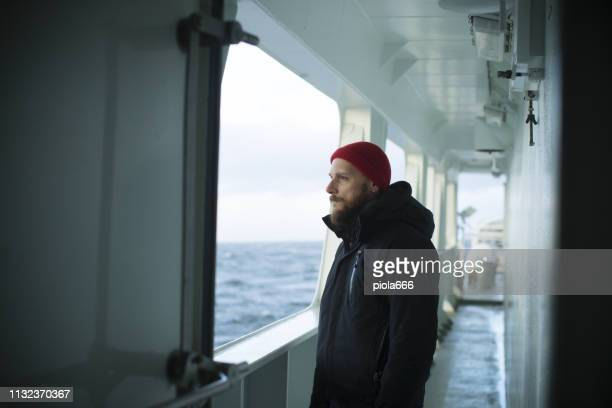 fisher man on the deck of a fishing boat - fishing boat stock pictures, royalty-free photos & images