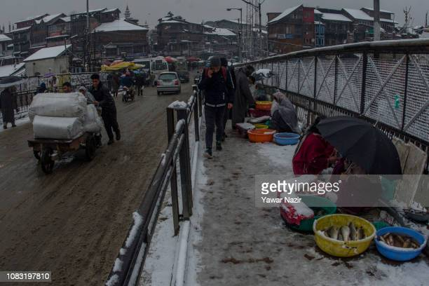 Fisher women sell fish on a snow covered footpath amid fresh snowfall on January 16 2019 in Srinagar the summer capital of Indian administered...