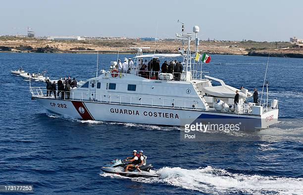 Fisherman accompany Pope Francis as he arrives in the port of the island on board of a Guardia Costiera boat on July 8, 2013 in Lampedusa, Italy. On...